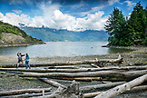 CANADA, Vancouver, British Columbia, Eric and Stepahnie Petersen hop across driftwood logs at Brigade Bay on Gambier Island, in the Howe Sound with the Britannia Range in the distance