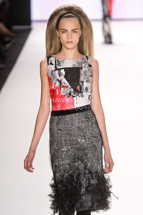 Cara Delevingne walks runway in a black, canvas and haute pink dress with silk poster print top and embroidered organza skirt, from the Carolina Herrera Fall 2012 collection, during Mercedes-Benz Fashion Week Fall 2012 in New York.