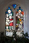 Stained glass window children singing playing music, church porch Saint Peter, Blaxhall, Suffolk, England, UK designed by Ellen Rope 1914