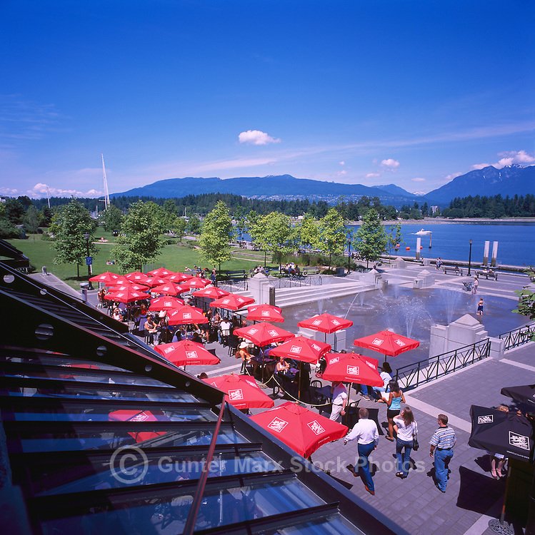 "People dining at the Mill Marine Bistro - an Outdoor Restaurant Cafe with Red Sun Umbrellas, and Children playing at Water Park, along Waterfront at ""Coal Harbour"", in the ""West End"" of Vancouver, British Columbia, Canada, in Summer.  The North Shore Mountains (Coast Mountains) rise in the background."