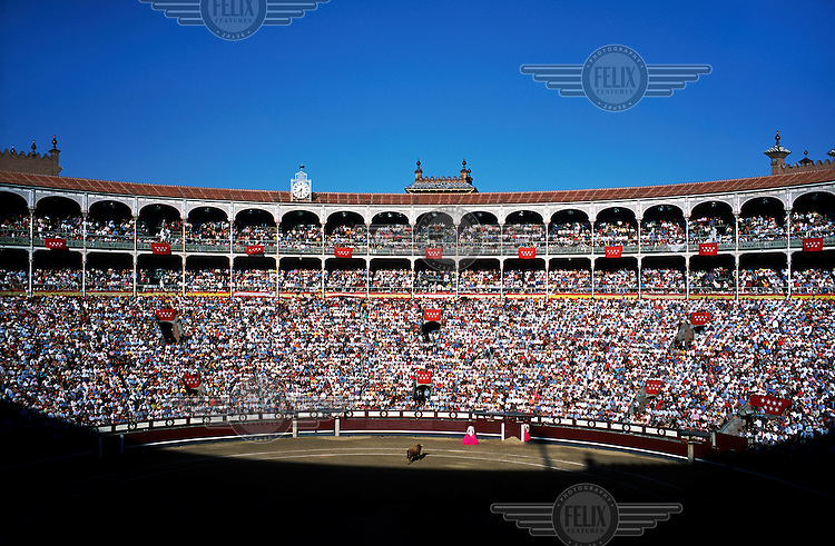 A packed crowd watch as a bull approaches a matador during a bullfight at the Plaza de Toros de las Ventas bullring in Madrid's Salamanca district..