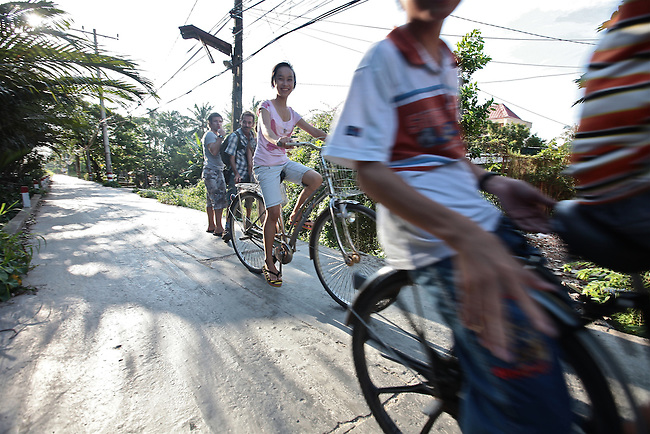 Children bicycle past a group of foreigners on a country road near the Saigon River outside Ho Chi Minh City, Vietnam. Aug. 11, 2011.