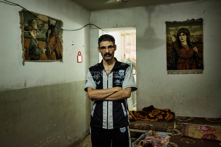 "29/08/15. Shaqlawa, Iraq. -- Imad, 38 y.o. from Falluja lives in a 12 square meters room in a basement of a disused building at the centre of the bazar, and for which he pays 300.00 IQD (250usd) per month. A former employee of the ministry of industry in Falluja, Imad lives with his wife and two children. He says ""we don't complain about the rats and mice: we live with them, we got used. But the snakes, those are dangerous, they are silent, and they bite."""