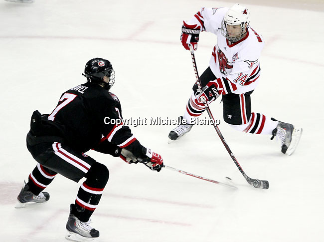 UNO's Joey Martin fires a shot as St. Cloud State's Kevin Gravel defends. UNO beat St. Cloud State 3-0 Friday night at Qwest Center Omaha.  (Photo by Michelle Bishop)