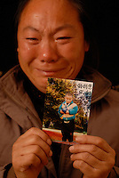 Mrs Hu holds a picture of her son Yang Yang,  who was stolen from under her nose, April 9th 2003.  Mrs Hu is one of thousands of migrant mothers whose children have been stolen and sold to rich families desperate for a boy. Families are limited to a single child under the China's ruthless One Child Policy.<br /> ©sinopix