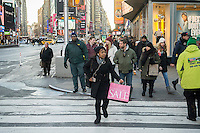 A woman crosses the street with her Victoria's Secret purchase in Times Square in New York on Tuesday, January 5, 2016. (© Richard B. Levine)