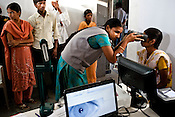 An official assists a young woman to get her iris scanned as part of the enrollment that is on its way in Naagaaram village, outskirts of Hyderabad in Andhra Pradesh, India. India is assigning each one of its 1.2 billion people a unique ID number based on digital finger prints and iris scan. Photograph: Sanjit Das/Panos