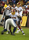 Washington Redskins quarterback Alex Smith (11) calls signals in the fourth quarter against the Dallas Cowboys at FedEx Field in Landover, Maryland on Sunday, October 21, 2018.  The Redskins won the game 20 - 17.  Preparing to block for Smith is Redskins offensive guard Shawn Lauvao (77). <br /> Credit: Ron Sachs / CNP