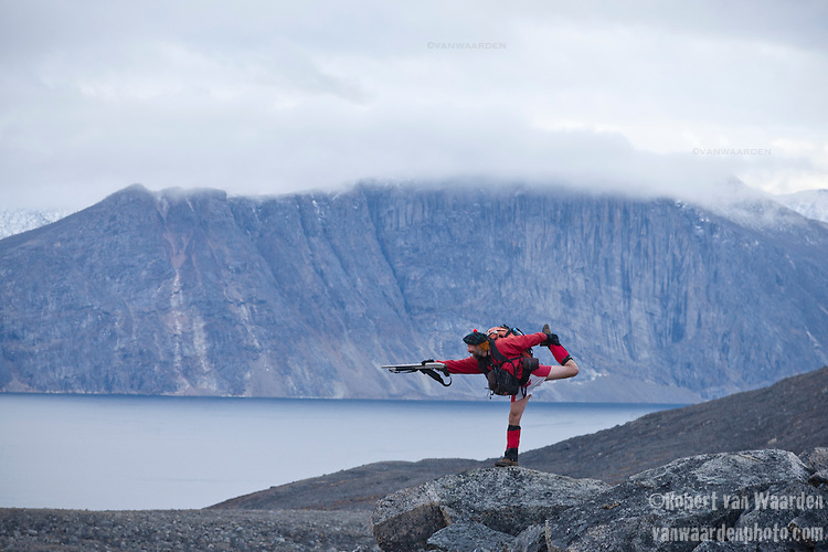 A man wearing Canadian flag (maple leaf) shorts and carrying a gun strikes a comic pose on a rock in Nunavut, Northern Canada.