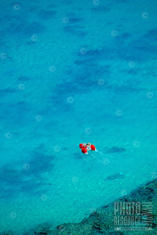 Relaxing shot of a tourist enjoying a ride on an ocean tricycle. Good color contrast of red cycle in the calm blue water.
