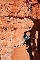 Female hiker enters tunnel on Queens Garden trail, Bryce Canyon national park, Utah, USA