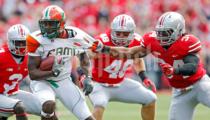Ohio State Buckeyes defensive end Jamal Marcus (34) tries to pull down Florida A&M Rattlers running back Al-Terek McBurse (1) in the 3rd quarter during their college football game at Ohio Stadium on September 21, 2013.  (Dispatch photo by Kyle Robertson)