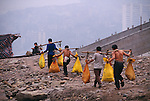 Line of stick-stick men (porters) carry bags from docks on the Yangtze River; commerce; city of Fuling, China, Asia; 041803