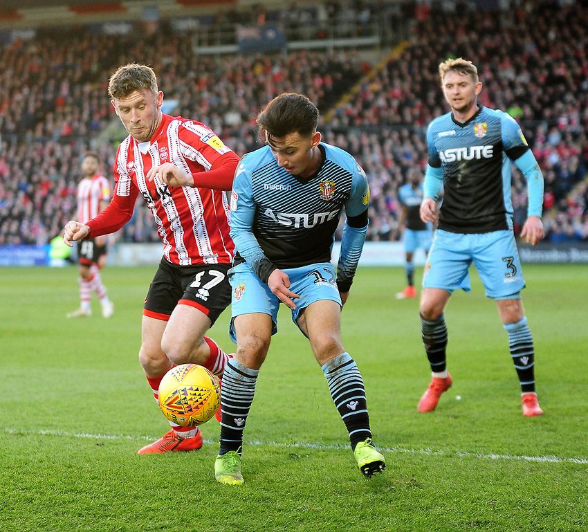 Lincoln City's Shay McCartan vies for possession with Stevenage's Ilias Chair<br /> <br /> Photographer Andrew Vaughan/CameraSport<br /> <br /> The EFL Sky Bet League Two - Lincoln City v Stevenage - Saturday 16th February 2019 - Sincil Bank - Lincoln<br /> <br /> World Copyright © 2019 CameraSport. All rights reserved. 43 Linden Ave. Countesthorpe. Leicester. England. LE8 5PG - Tel: +44 (0) 116 277 4147 - admin@camerasport.com - www.camerasport.com