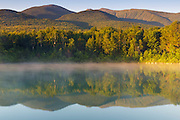 Fog on Durand Lake in Randolph, New Hampshire  at sunrise during the summer months. The Northern Presidential Range is reflecting in the water.