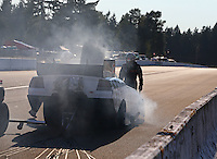 Aug. 1, 2014; Kent, WA, USA; NHRA funny car driver Paul Lee walks away from his smoking car during qualifying for the Northwest Nationals at Pacific Raceways. Mandatory Credit: Mark J. Rebilas-