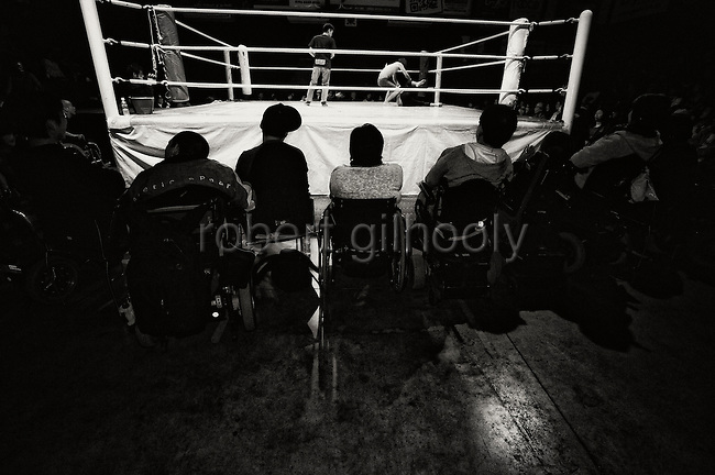 Wheelchair-bound fans watch a wrestling bout at Doglegs, an event for wrestlers with physical and mental handicaps in Tokyo, Japan.