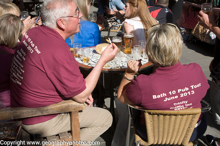 A crowd of people on a pub crawl drinking outside a pub in Bath, Somerset, England