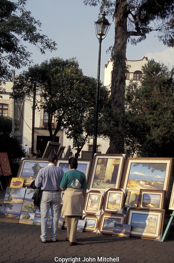 Couple looking at paintings at the Bazar Sabado, the Saturday bazaar held in San Angel, a suburb of Mexico City