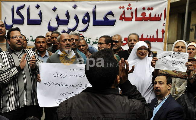 Egyptian workers and employees of Industrial and Engineering Enterprises Co, take part in a protest demanding for their salaries, outside Egyptian cabinet, in Cairo on December 14, 2014 . Photo by Amr sayed