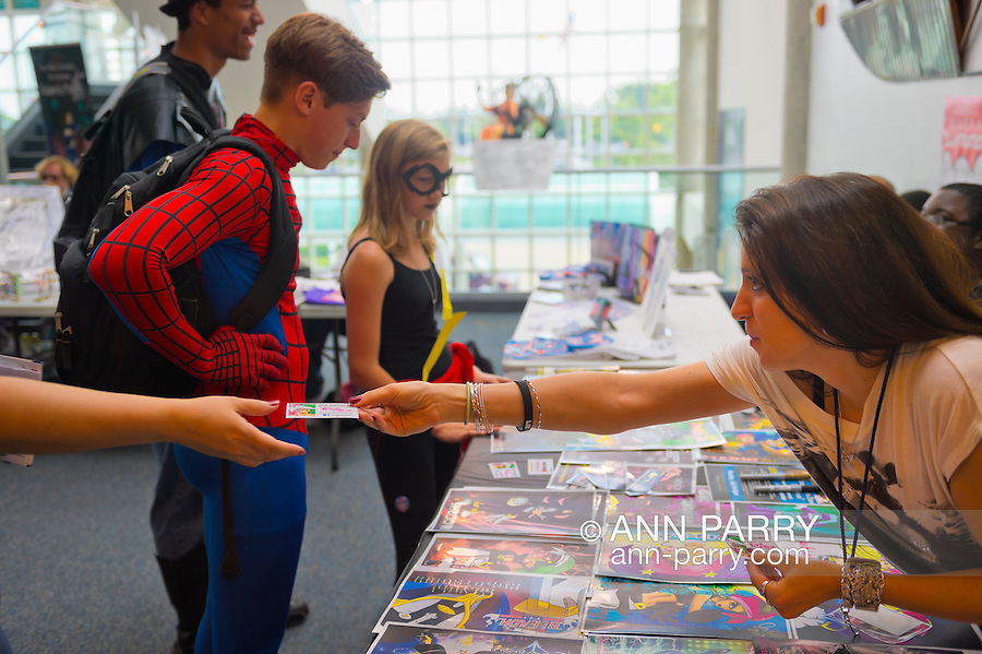 Garden City, New York. 15th June 2013. Artist JEN SCRIMENTI hands her business card to a visitor, while others dressed in super hero costumes look at artowrk, at Artists Alley at Eternal Con Pop Culture Expo, which was hosted by the Cradle of Aviation Museum of Long Island.