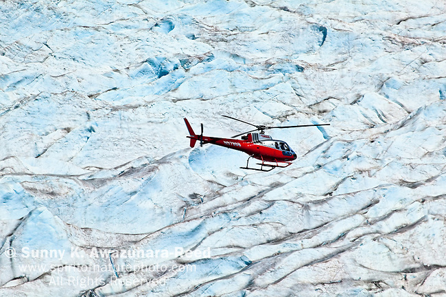 A helicopter tour fly over Mendenhall Glacier, Juneau, SE Alaska on a sunny day.