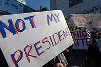 "A sign saying ""Not my President"" at the Vote Out the Scandal rally at Hachiko Square, Shibuya, Tokyo, Japan. Sunday November 5th 2017. Timed to coincide with President Trumps visit to Japan, About 120 Americans living in Japan and some local Japanese  protested together from 2pm to 4pm to encourage US citizens to register to vote in future elections and call on the US government to honour it responsibilities to the American people,."