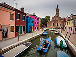 A blue boat travels a canal toward the church and leaning tower, the colorful village of Burano, Italy.