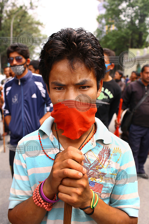 A portrait of a masked protester holding a stick at a strike called by the Unified Communist Party of Nepal (UCPN) to remove the ruling government. The Maoist opposition blocked streets leading to key government offices on the 6th May, the fifth day of their crippling general strike to demand the prime minister's resignation, but the government has vowed not to bow to the protesters' pressure. The Maoists, known to use violence to back their strike calls, have demanded that residents halt all travel and keep businesses and schools closed since Sunday in their campaign to get Prime Minister Madhav Kumar Nepal to resign and hand power to a Maoist-led government. The strike has shut down most businesses, schools and transport, with daily activity grinding to a standstill.