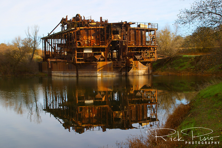 Constructed in 1933 at a cost of $543,148 the Tuolomne Gold Dredge has sat idle since 1951. Located near the former mining town of La Grange, in California's Gold Country, the dredge weighed over 2500 tons and floated on its own self-created pond of water. The dredge's boom consisted of 120 buckets weighing 4000 pounds each that extended 70 feet below the waters surface. The total amound of gold recovered by the dredge is not known. The dredge is registered as historic landmark #1971000208. Photographed 12/05