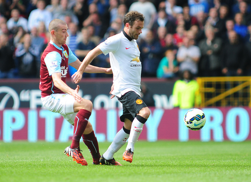 Manchester United's Juan Mata shields the ball from Burnley's David Jones<br /> <br /> Photographer Chris Vaughan/CameraSport<br /> <br /> Football - Barclays Premiership - Burnley v Manchester United - Saturday 30th August 2014 - Turf Moor - Burnley<br /> <br /> &copy; CameraSport - 43 Linden Ave. Countesthorpe. Leicester. England. LE8 5PG - Tel: +44 (0) 116 277 4147 - admin@camerasport.com - www.camerasport.com