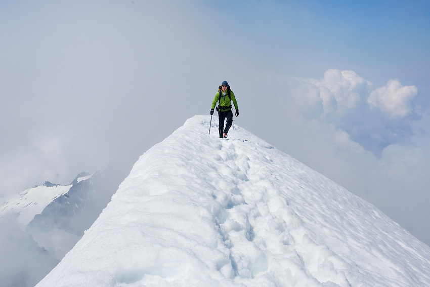 """WALKING THE RIDGE"" -- A mountaineer walks along the knife edge summit ridge of El Dorado Peak in Washington's North Cascades National Park. Summer."