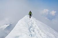 """WALKING THE RIDGE"" -- A mountaineer walks along the knife edge summit ridge of El Dorado Peak in Washington's North Cascades National Park. Summer."
