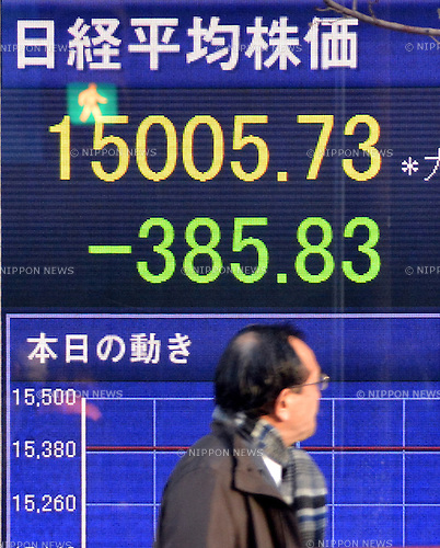 January 27, 2014, Tokyo, Japan - A pedestrian scurries past the electric bulletin board of a Tokyo brokerage showing the closing quote of Monday's trading on the Tokyo Stock Exchange market on January 27, 2014. Tokyo stocks traded sharply lower with the Nikkei Stock Average briefly falling below the 15,000 mark for the first time in about two months. The Nikkei index closed at 1,5005.73, down 385.83 points from Friday.  (Photo by Natsuki Sakai/AFLO)