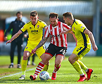 Lincoln City's Neal Eardley powers betweenCheltenham Town's Kevin Dawson, left, and Chris Hussey<br /> <br /> Photographer Andrew Vaughan/CameraSport<br /> <br /> The EFL Sky Bet League Two - Lincoln City v Cheltenham Town - Saturday 13th April 2019 - Sincil Bank - Lincoln<br /> <br /> World Copyright &copy; 2019 CameraSport. All rights reserved. 43 Linden Ave. Countesthorpe. Leicester. England. LE8 5PG - Tel: +44 (0) 116 277 4147 - admin@camerasport.com - www.camerasport.com