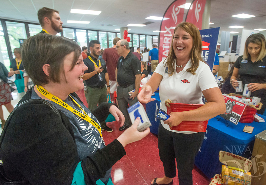 NWA Democrat-Gazette/BEN GOFF @NWABENGOFF<br /> Whitney Perkins (left), a teacher at Southwest Junior High, gets a free stapler from Julie Shook with Arvest Bank, who's daughter attends Southwest, Thursday, Aug. 9, 2018, during the 52nd Annual Sam's Furniture Springdale Teacher Appreciation Day at Springdale High School. Arvest Bank was handing out free staplers to teachers at the event. More than 85 vendors set up to provide information and more than $40,000 in gifts and prizes to some 2,000 teachers and staff of Springdale Public Schools.