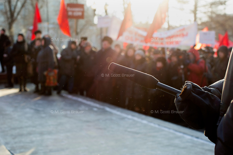 A reporter holds a microphone during a legal Communist Party (KPRF) demonstration in Moscow, Russia.