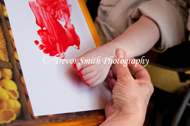 Child with learning disabilities using foot to paint a picture