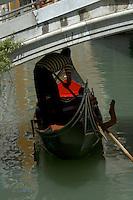 Gondalier bending, as he navigates his gondala under bridge. Venice, Italy.