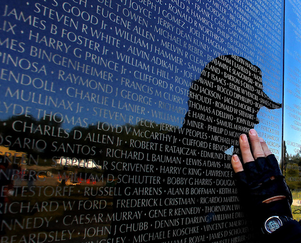 A veteran touches a panel bearing names of those killed or missing in the Vietnam War during assembly of The Dignity Memorial Vietnam Experience September 14 at Resthaven Cemetery in West Des Moines.