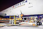 A ground crew member opens cargo after the arrival of a Delta 777 flight from Johannesburg, South Africa at Gate F8 outside of the Maynard H. Jackson Jr. International Terminal at Hartsfield–Jackson Atlanta International Airport, in Atlanta, Georgia on August 28, 2013.