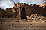 November 2012, Bamiyan, Afghanistan: Local kids play football in front of the empty Buddhas of Bamiyan niches, two 6th century monumental statues of standing buddha carved into the side of a cliff in the Bamyan valley in the Hazarajat region of central Afghanistan.The valley is home to many Hazara's, who have often made up vast numbers of refugees to Australia, having been persecuted and driven from their homes in both Afghanistan as well as from Quetta in Pakistan where a lot of displaced Hazara fled to during the Taliban years. Bamiyan is home to a lot of Hazara who are Shia muslim and as such are looked down upon by the Sunni Pashto tribes that make up the population majority in Afghanistan.   Picture by Graham Crouch/The Australian Magazine.