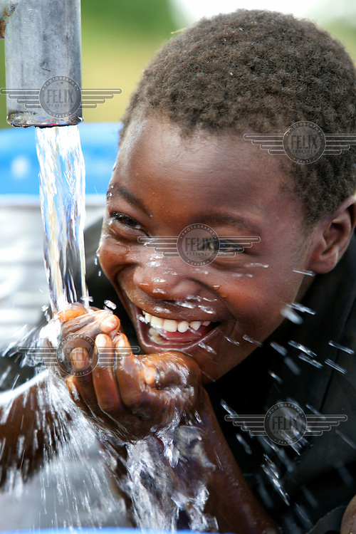 A boy drinking clean water from a pump.