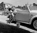 Bethel Park PA:  View of Michael Stewart washing the Stewart's new Volkswagen Beetle convertible - 1961.