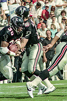 Chris Miller, #12, Atlanta Falcons, hands off to Mike Rozier, #30, Atlanta Falcons, Atlanta Falcons at Tampa Bay Buccaneers.  The Bucs beat the Falcons 23-17  at Tampa Stadium on December 2, 1990, Tampa, Florida.  (Photo by Brian Cleary/bcpix.com)