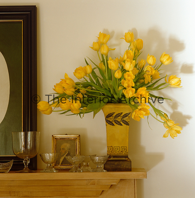 A vase filled with yellow tulips stands on the mantelpiece which is decorated with antique glassware
