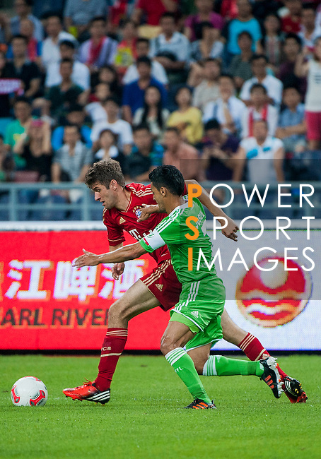 Thomas Muller of Bayern Munich and Josue of VfL Wolfsburg in action during a friendly match as part of the Audi Football Summit 2012 on July 26, 2012 at the Guangdong Olympic Sports Center in Guangzhou, China. Photo by Victor Fraile / The Power of Sport Images