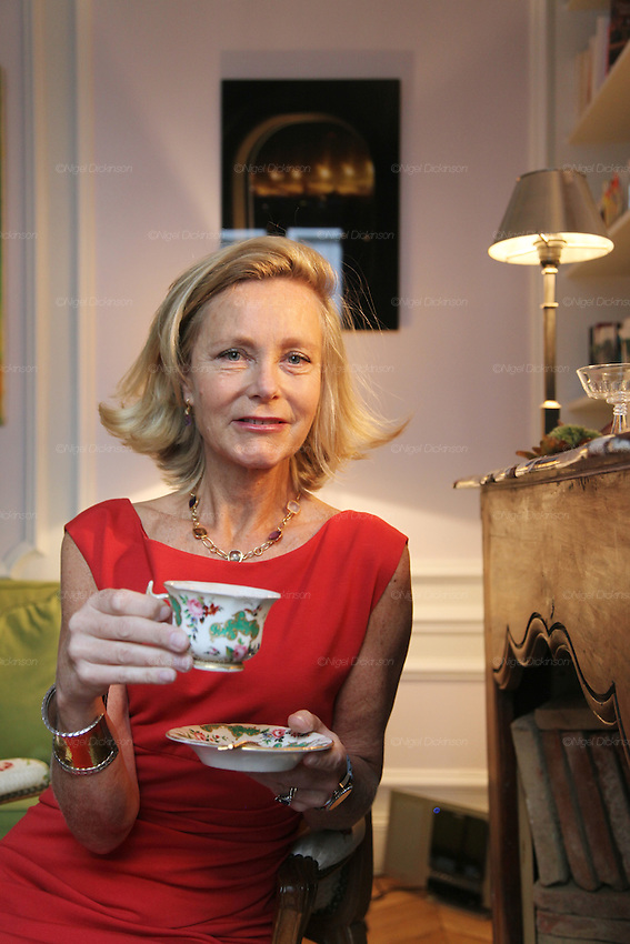 Marie de Tilly poses with a cup and saucer of tea in her apartment..Marie de Tilly gives lessons on French Etiquette. She lives in a bijou Hausman apartment in central Paris, not far from the Champs Elysées. She has trained people with these skills for several years; working across the Paris area and even takes her work worldwide, giving classes to a range of people. She is especially popular in Russia and the ex-Soviet countries such as Kasakhstan. Her skills are sought after by individuals, families and businessmen wishing to aspire to enter French High Society. Her students, whether they are Russian or French, want to learn the necessary airs and graces to blend seemlessly into Parisian haute societé. Paris, France