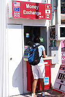 Young woman exchanging money at a booth in Playa del Carmen, Riviera Maya, Quintana Roo, Mexico.