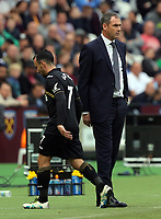 Leon Britton of Swansea City (L) walks past Swansea manager Paul Clement during the Premier League match between West Ham United v Swansea City at the London Stadium, London, England, UK. Saturday 30 September 2017